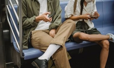 crop couple browsing smartphones in subway carriage